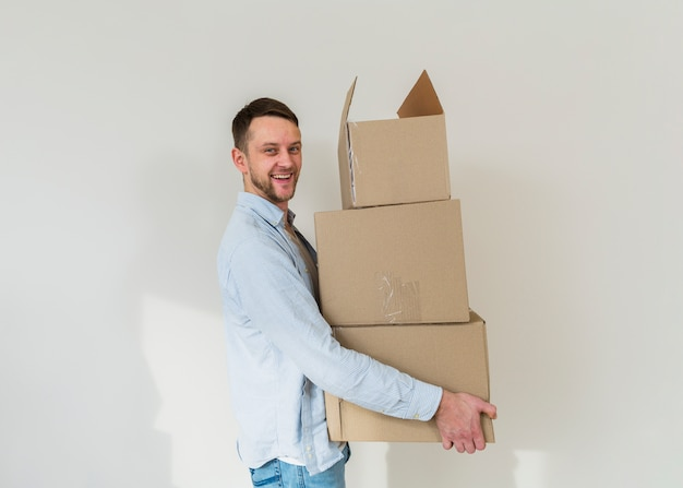 Portrait of a smiling young man carrying stack of cardboard boxes against white wall