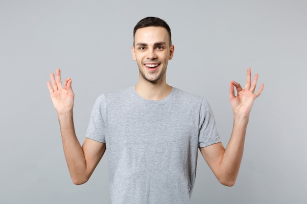 Ritratto di un giovane sorridente in abiti casual che si tiene per mano in un gesto di yoga rilassante meditando