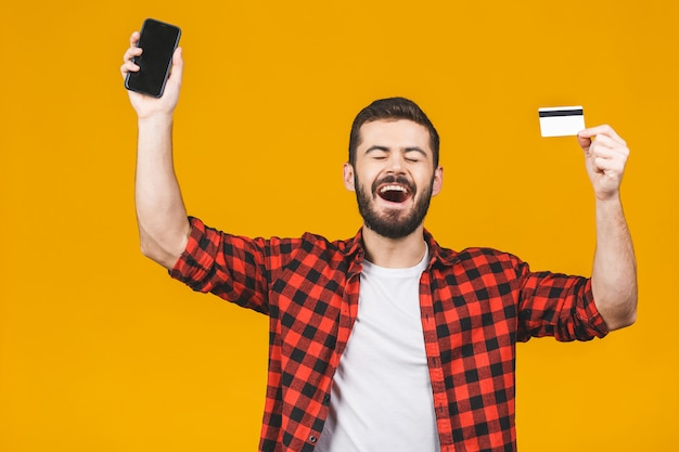 Portrait of a smiling young man holding blank screen mobile phone and showing credit card isolated over yellow wall.