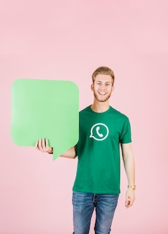Portrait of a smiling young man holding empty green speech bubble