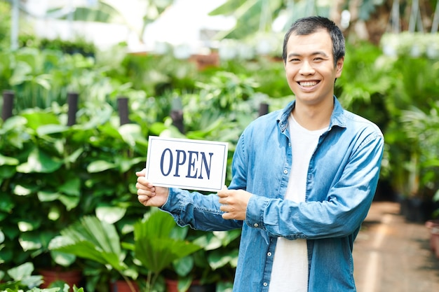 Portrait of smiling young man opening plant nursery and inviting customers