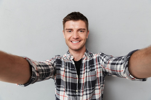 Portrait of a smiling young man in plaid shirt