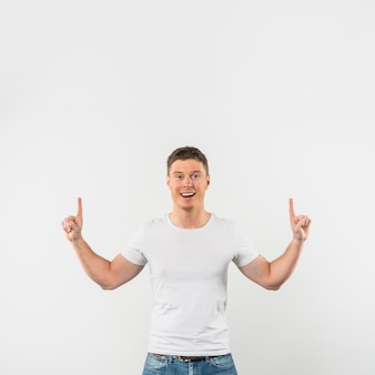 Portrait of a smiling young man pointing fingers upward against white background