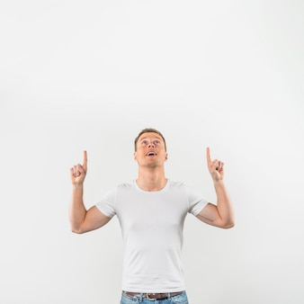 Portrait of a smiling young man pointing fingers upward looking up against white background