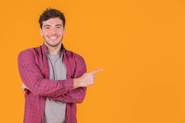 Portrait of a smiling young man pointing his finger against an orange backdrop