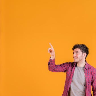 Portrait of a smiling young man pointing his finger against orange background