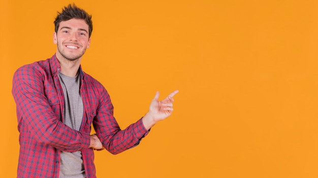 Portrait of a smiling young man pointing his finger at something against orange backdrop