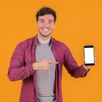Portrait of a smiling young man showing his mobile phone against an orange backdrop