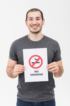 Portrait of a smiling young man showing no smoking sign isolated on white backdrop