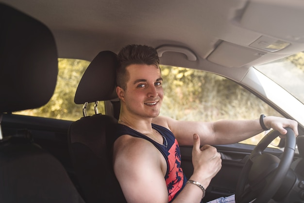 Portrait of smiling young man sitting in a car and looking at the camera on a sunny day