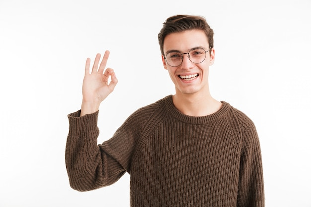 Portrait of a smiling young man in sweater showing ok