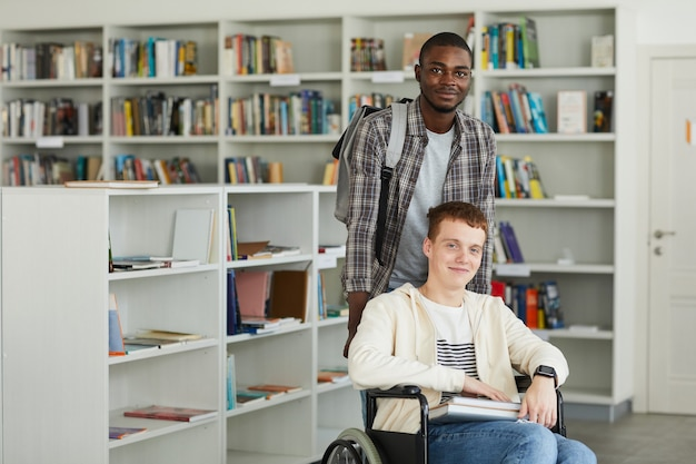 Portrait of smiling young man using wheelchair in school library with african-american man helping him and ,
