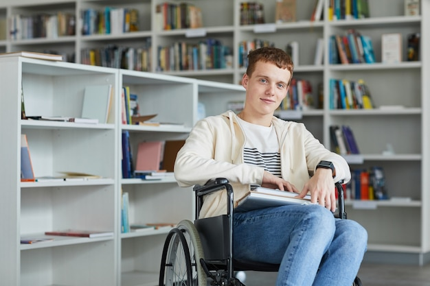 Portrait of smiling young man using wheelchair in school library and ,