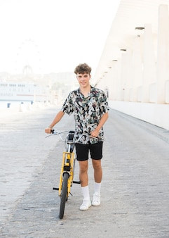 Portrait of a smiling young man with bicycle