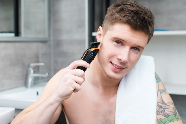Portrait of a smiling young man with towel on his shoulder shaving with electric razor in the bathroom
