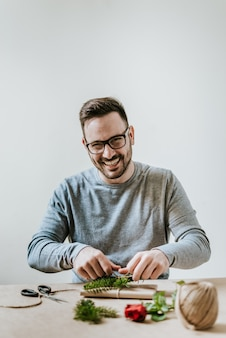 Portrait of smiling young man wrapping present.valentine, birthday or anniversary concept.