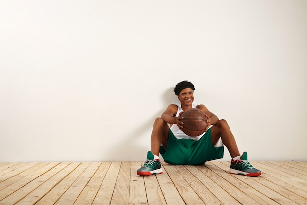 A portrait of an smiling young player sitting on the wooden floor against a white wall holding an old brown basketball