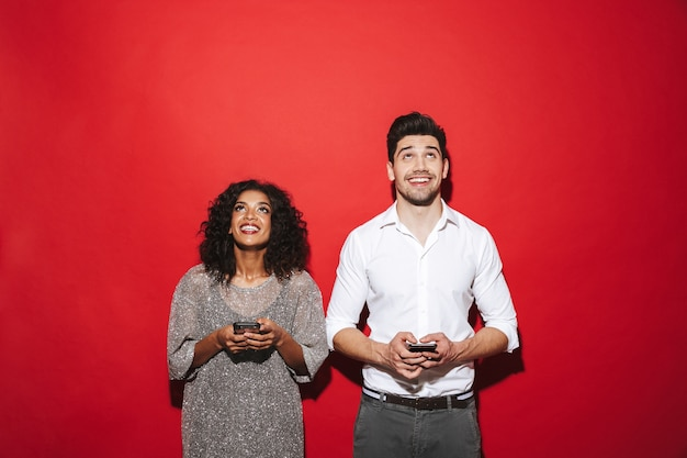 Portrait of a smiling young smartly dressed couple standing isolated over red space, using mobile phones