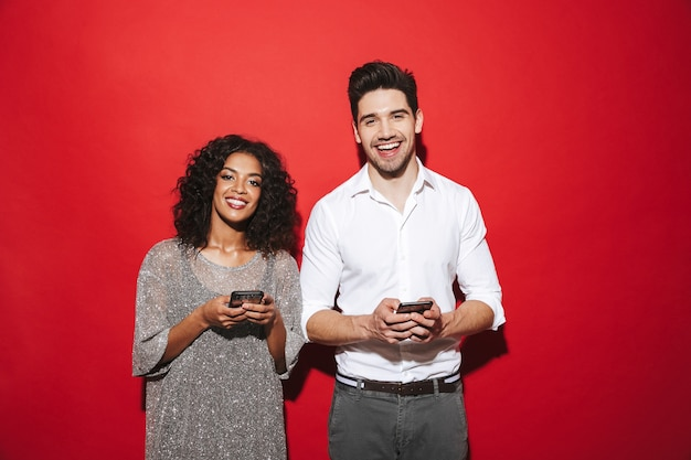 Portrait of a smiling young smartly dressed couple standing isolated over red space