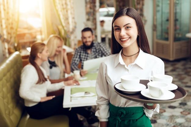 カフェに立っている笑顔若いウェイトレスの肖像画