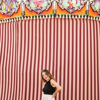 Ritratto della giovane donna sorridente al parco di divertimenti