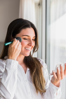 Portrait of a smiling young woman applying the face powder with makeup brush