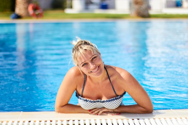 Portrait of a smiling young woman on a background of blue water of a pool