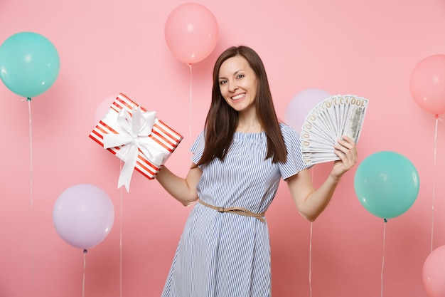 Portrait of smiling young woman in blue dress holding bundle lots of dollars cash money and red box with gift present on pink background with colorful air balloons. birthday holiday party concept.