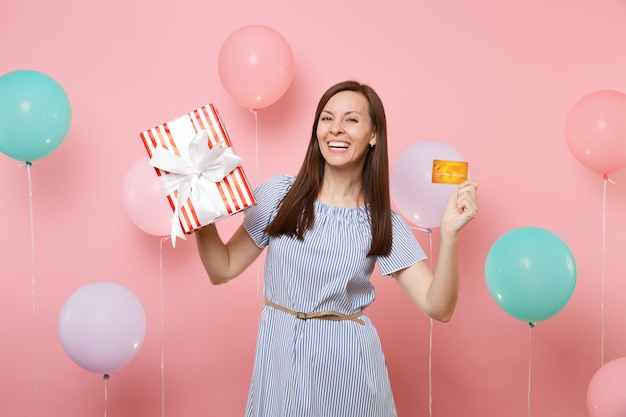 Portrait of smiling young woman in blue dress holding credit card and red box with gift present on pastel pink background with colorful air balloons. birthday holiday party, people sincere emotions.