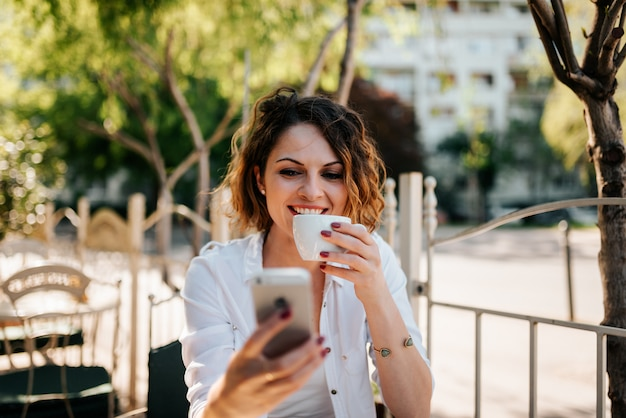 Portrait of a smiling young woman drinking coffee and using smartphone outdoors.