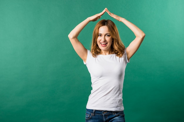 Portrait of a smiling young woman forming house gesture against green background