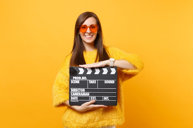 Portrait of smiling young woman in fur sweater, orange heart eyeglasses hold classic black film making clapperboard isolated on yellow background. people sincere emotions, lifestyle. advertising area.
