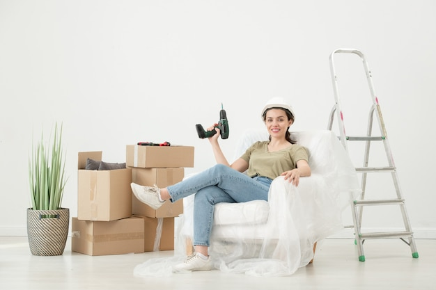 Portrait of smiling young woman in hardhat sitting with cordless screwdriver in armchair under cover in room with moving boxes