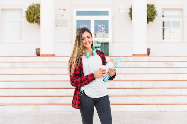 Portrait of a smiling young woman holding books in hand standing against university building