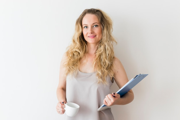Portrait of smiling young woman holding clipboard and white coffee cup