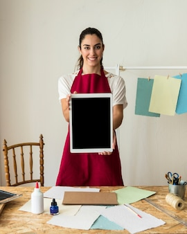 Portrait of a smiling young woman holding digital tablet