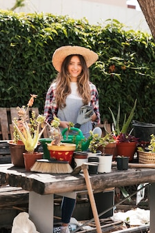 Portrait of a smiling young woman holding gardening gloves standing behind the plants on table