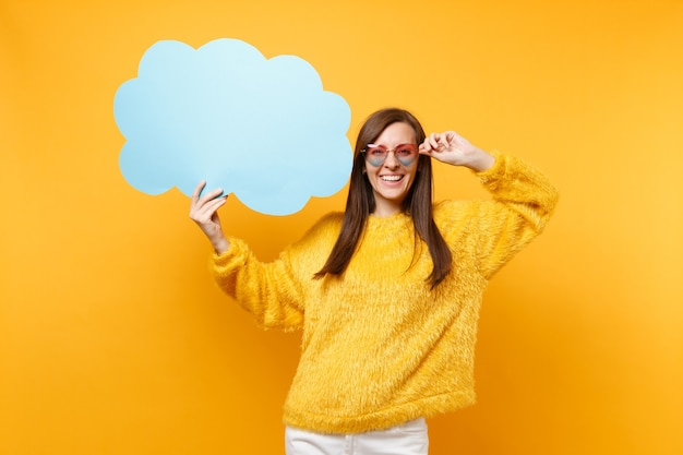 Portrait of smiling young woman holding heart eyeglasses, empty blank blue say cloud, speech bubble isolated on bright yellow background. people sincere emotions, lifestyle concept. advertising area.