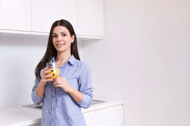 Portrait of a smiling young woman holding juice glass in hand looking at camera