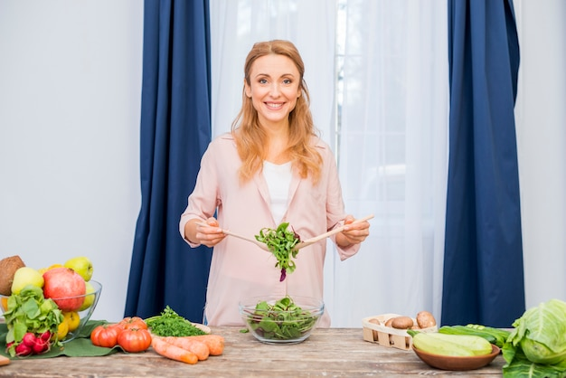 Portrait of a smiling young woman holding leafy vegetable with wooden spoon in the bowl