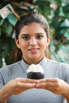 Portrait of smiling young woman holding pastry