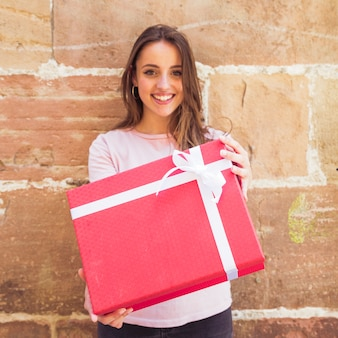 Portrait of a smiling young woman holding red gift box against wall