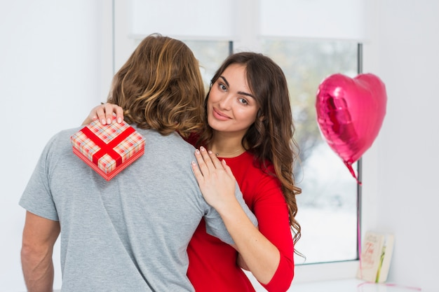 Portrait of a smiling young woman holding red gift box embracing her boyfriend