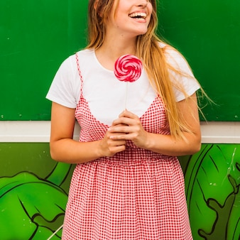 Portrait of a smiling young woman holding red lollipop in hand