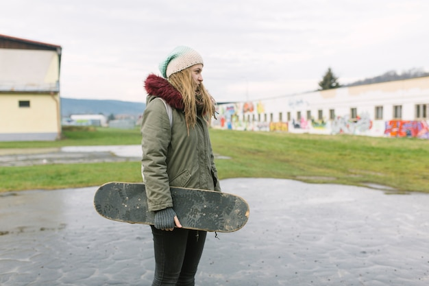 Portrait of smiling young woman holding skateboard in the park