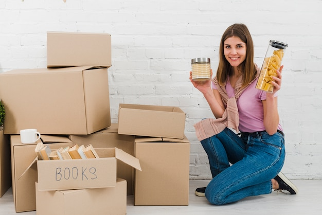 Portrait of a smiling young woman holding snack bottles kneeling near their piles of cardboard boxes