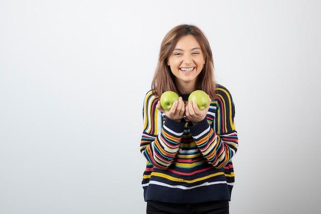 Ritratto di una giovane donna sorridente che tiene due mele verdi fresche.