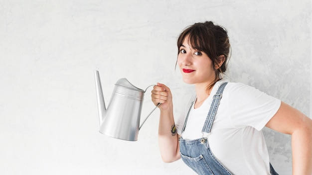 Portrait of a smiling young woman holding watering can