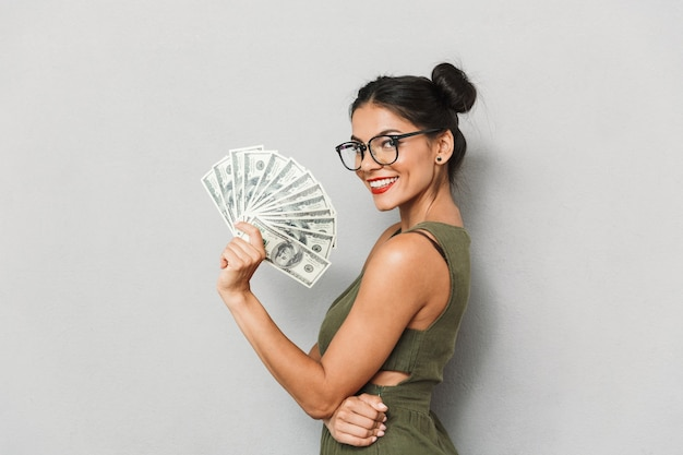 Portrait of a smiling young woman isolated, showing money banknotes