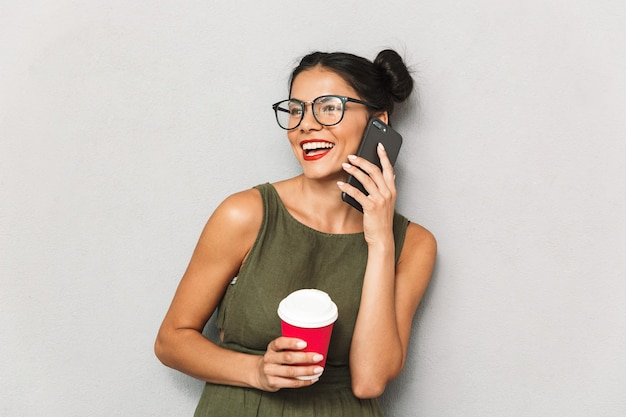 Portrait of a smiling young woman isolated, talking on mobile phone, holding takeaway coffee cup